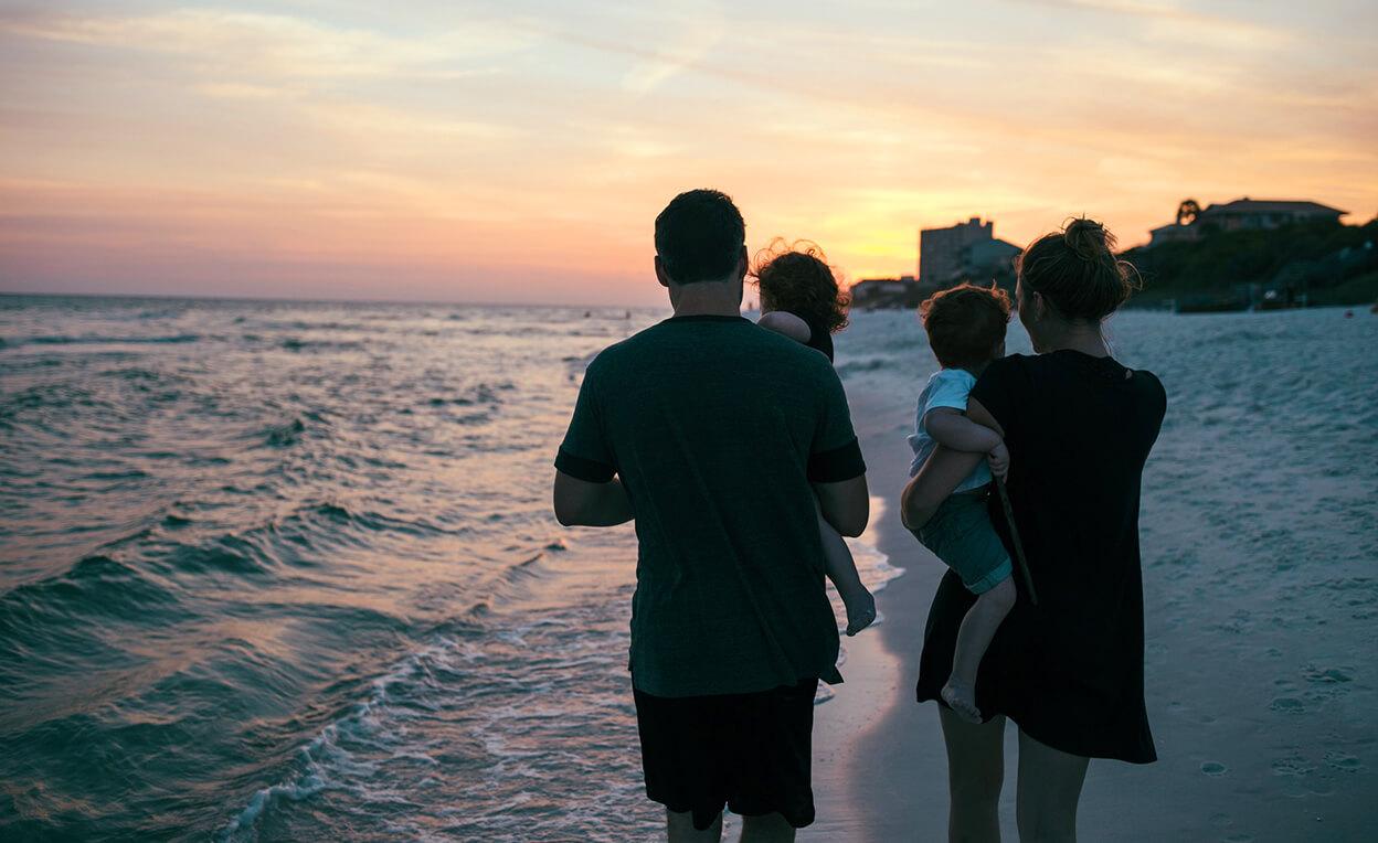 夕日の海辺にいる家族