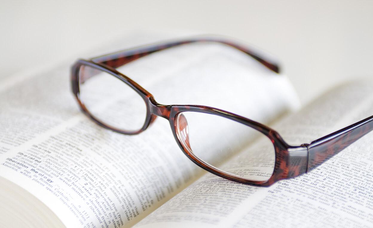 辞書の上に置かれたメガネ