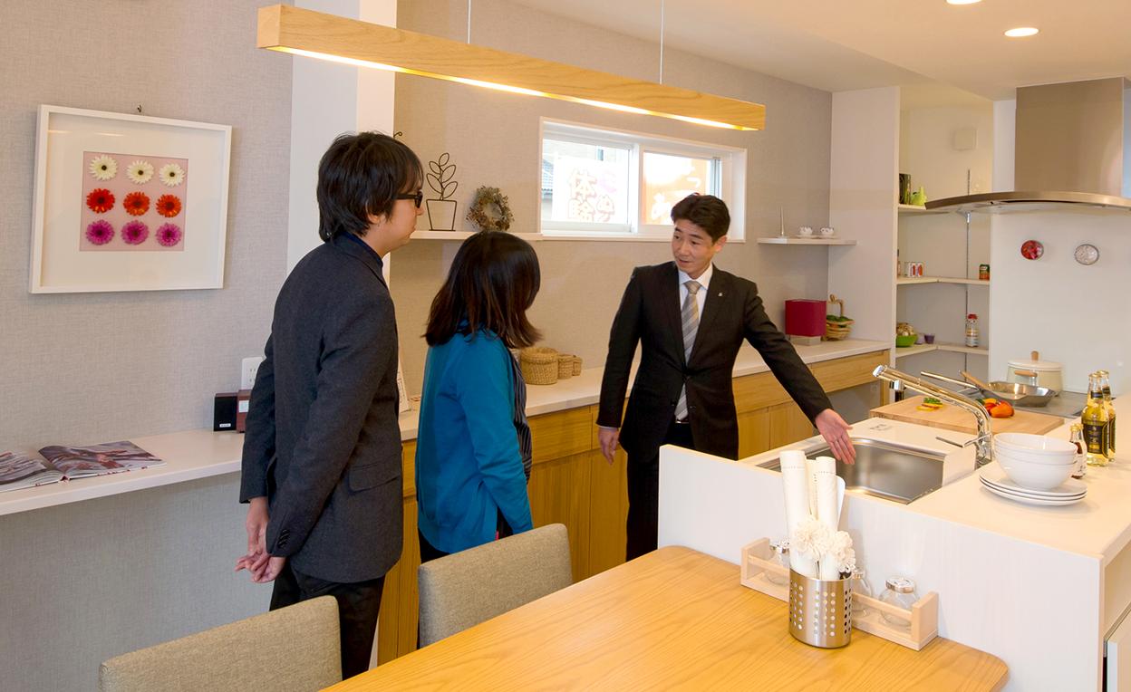 ユニバーサルホーム伊予西条店モデルハウスのキッチンで説明を受ける夫婦