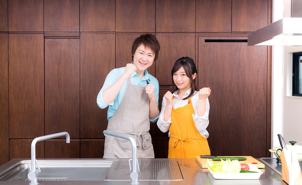 キッチンでガッツポーズをする夫婦